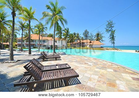 Beach Chair, Palm Trees And Pool At The Resort At Seaside