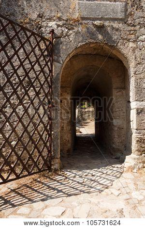 Acient weathered stone gate with metal door