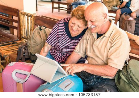 Happy Senior Couple Sitting With Digital Laptop And Travel Baggage At Adventure Trip Around World