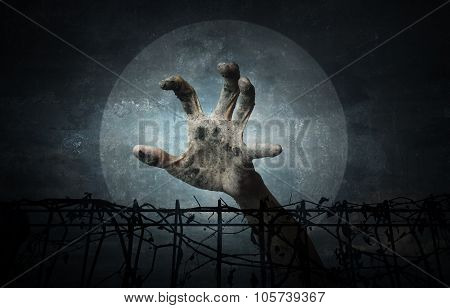 Hand Over Metal Fence With Dry Leaves Over Dark Sky And Moon, Halloween Concept