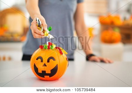 Woman Putting Trick Or Treat Candy In Halloween Bucket. Closeup