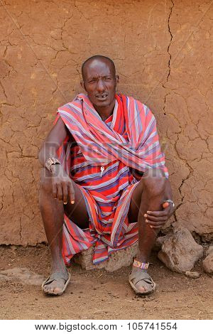 AMBOSELI, KENYA - AUGUST 31, 2013:Unidentified Masai man with traditional colorful garment sitting in front of his hut in a rural village, Amboseli, Kenya