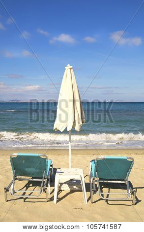 Sunbathing chairs and umbrella on St-Georges beach in Naxos, Greece