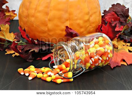 Candy Corn In A Mason Jar Spilling Onto A Table Decorated For Autumn.