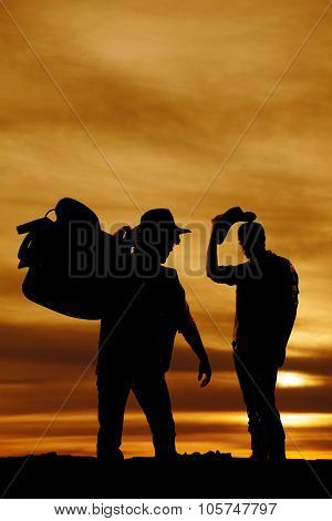 Silhouette Of Two Cowboys In The Sunset One Hold Saddle On Shoulder