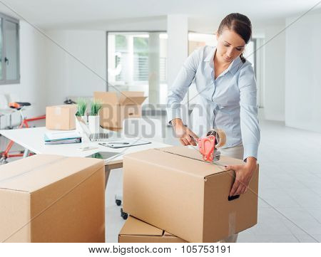 Businesswoman Taping Up A Cardboard Box