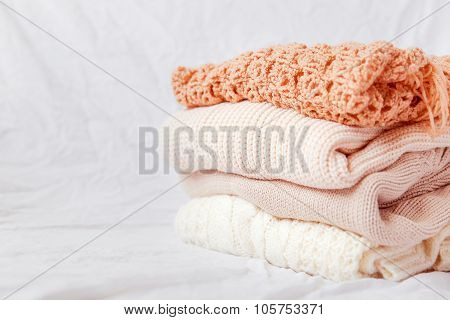 Pile Of Beige Woolen Clothes On A White Background.