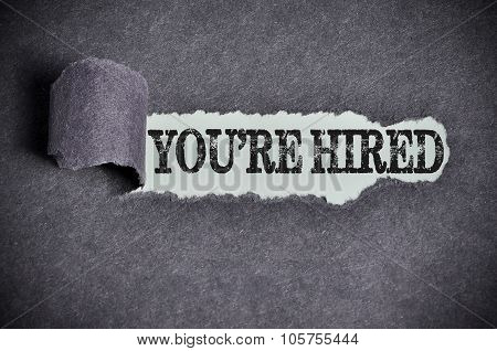 You're Hired Word Under Torn Black Sugar Paper