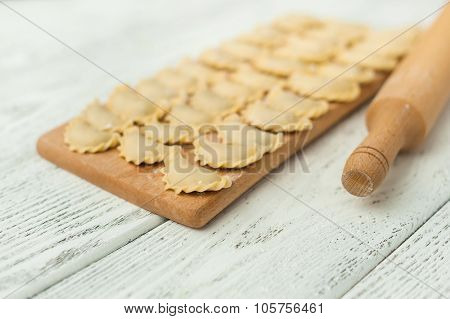 Uncooked dumplings on the wooden desk.