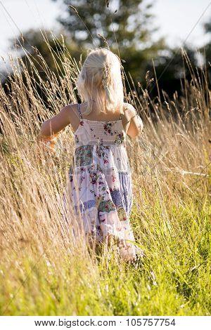 Little Girl Walking Away Though The Grass