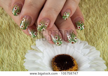 spring fingernails with a flower and on the green towel, comomile