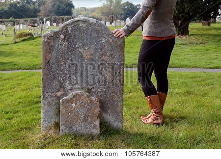 Woman Rests Her Hand Thoughtfully On A Headstone