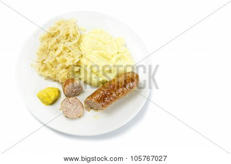 Bratwurst With Sauerkraut, Mashed Potatoes And Mustardon A Plate, Isolated On White