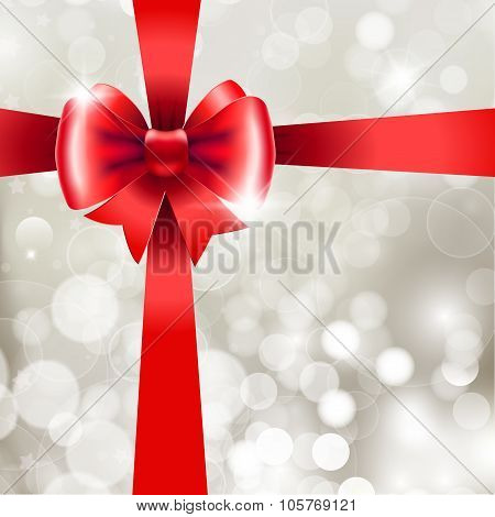 Red Ribbon With Bow On Silver Background.