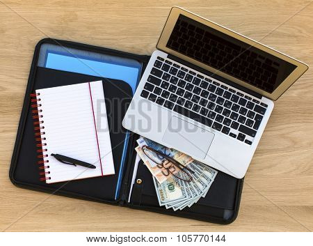 Business background - detailed business case with laptop, open notebook and dollars/euros bills. Top view of wooden texture of the table.