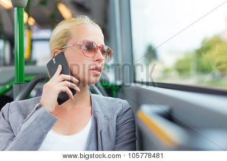 Blonde business woman traveling by bus.
