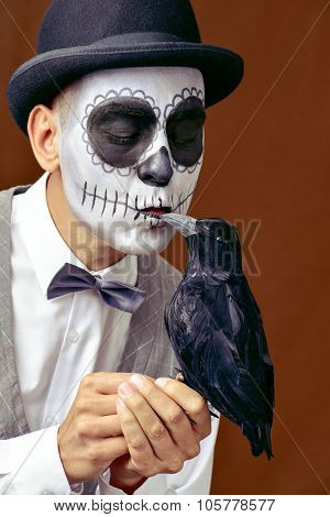 portrait of a man with mexican calaveras makeup, wearing bow tie and bowler hat, kissing a black crow