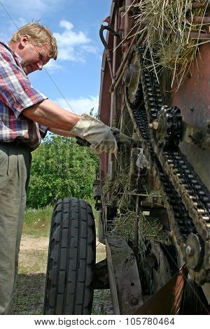 Farm Equipment Mechanic Lubricates Engine Oil Roller Chain Mechanism Baler.