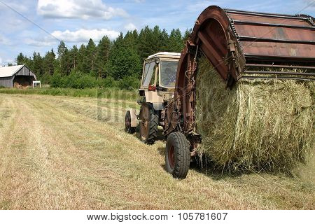 Farm Tractor Pulls Round Baler Whilst Hay Making.