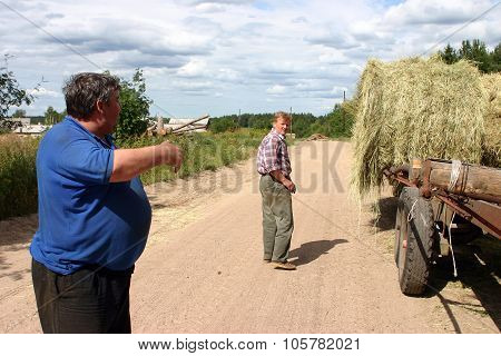 Russian Farmers Talking About The Trailer With Bales Of Hay.