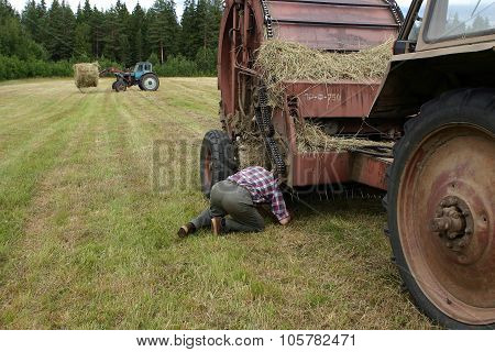 Russian Farmer Tractor-driver Repairs Baler Hay In The Field.