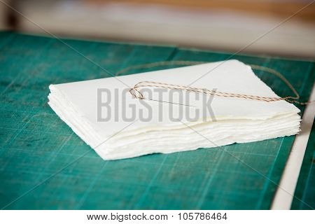 Closeup of needle with thread and papers on table in factory