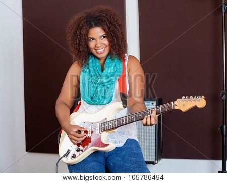 Smiling young woman playing guitar in recording studio