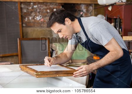 Mid adult male worker using tweezers to clean paper in factory