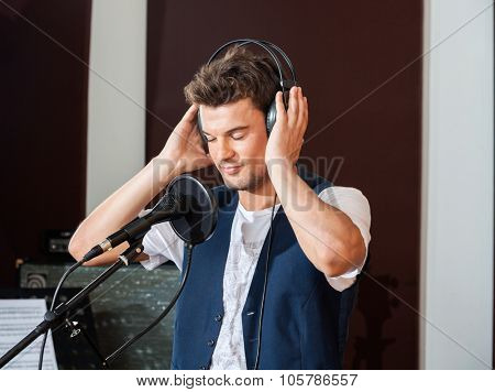 Young male singer listening carefully to music through headphones in recording studio