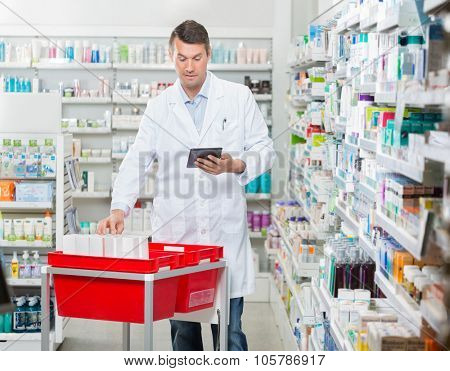 Mid adult male pharmacist counting stock while using digital tablet at drugstore