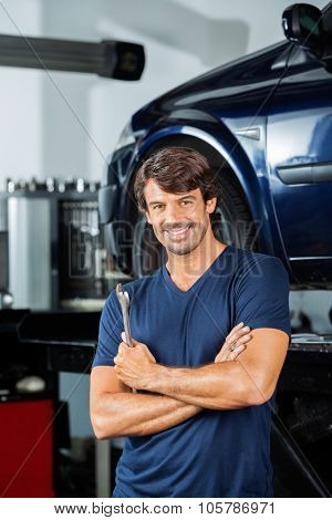 Portrait of confident mechanic holding wrench while standing arms crossed at garage