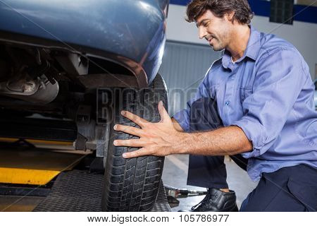 Male mechanic changing car tire at auto repair shop