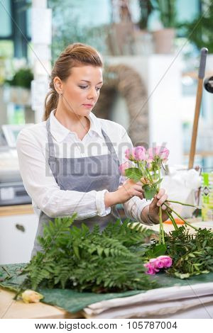 Florist making rose bouquet at counter in flower shop