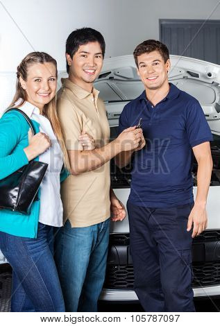 Portrait of happy couple giving keys to technician while standing in front of car at auto repair shop