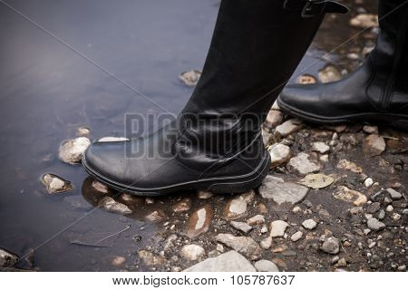 female leg in black  leather high boots on cobble on the edge of rain puddle, closeup, selective focus