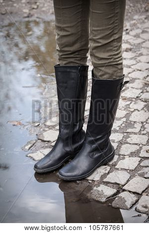 female legs in black  leather high boots on cobble on the edge of rain puddle, closeup