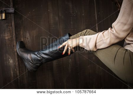woman hand pull on black leather high flat boots on dark wooden background, closeup, outdoors, selective focus