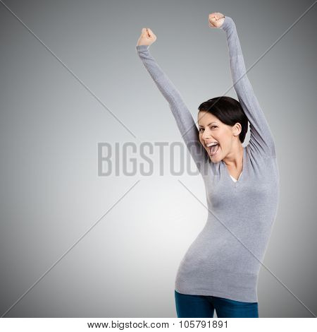 Beautiful girl gesturing triumphal fists puts her hands up, isolated on grey background