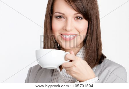 Beautiful business woman drinking coffee from white cup, isolated on white