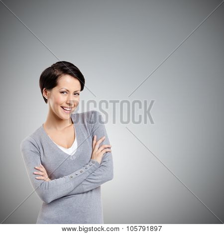 Smiley woman with crossed arms, on grey background