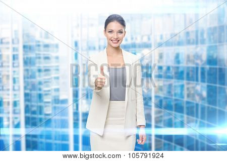Portrait of businesswoman who thumbs up, modern blue background. Concept of leadership and success