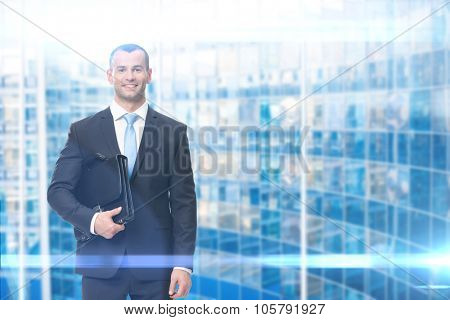 Portrait of businessman keeping black leather suitcase, blue background