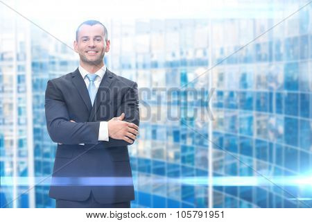 Portrait of businessman with hands crossed, blue background. Concept of leadership and success