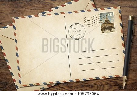 Old vintage postcard and envelope with pen on table