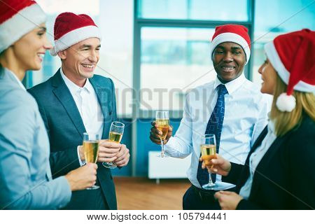Modern office workers in Santa caps celebrating Christmas after work