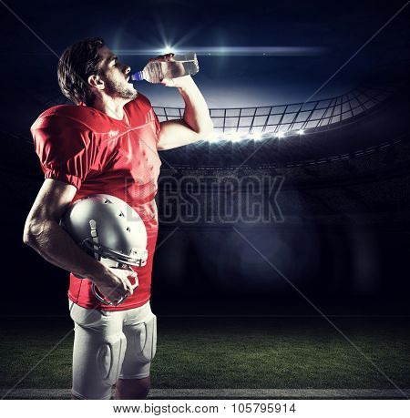 Thirsty American football player in red jersey drinking water against american football arena