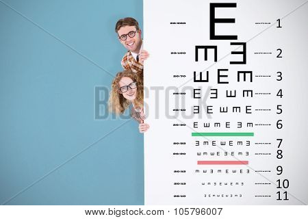 Geeky hipster holding poster and smiling at camera against blue background
