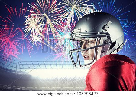 Side view of American football player looking away against fireworks exploding over football stadium
