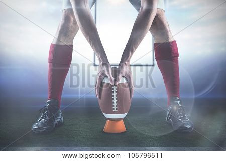 Low section of sports player placing the ball against american football arena