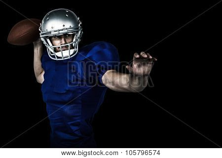 American football player throwing ball against black